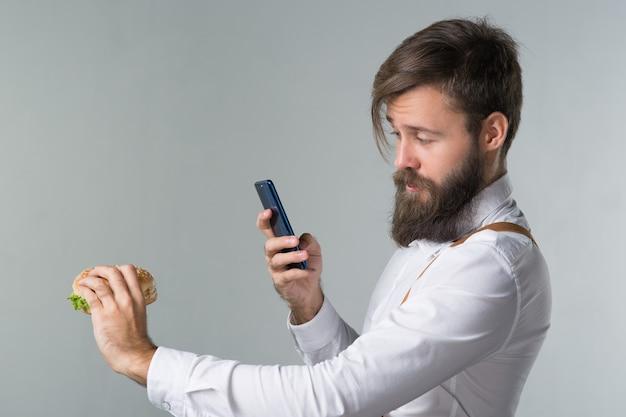 Мужчина с бородой в белой рубашке и подтяжках ест нездоровую пищу из гамбургера быстрого питания или чизбургера и фотографирует еду на смартфоне на сером фоне