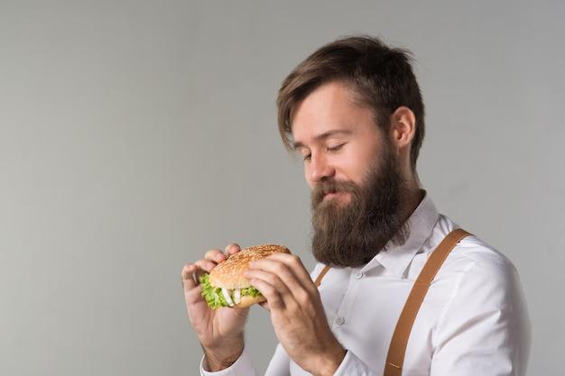白いシャツのひげと灰色の背景にファーストフードのハンバーガーまたはチーズバーガーからジャンクフードを食べるサスペンダーを持つ男
