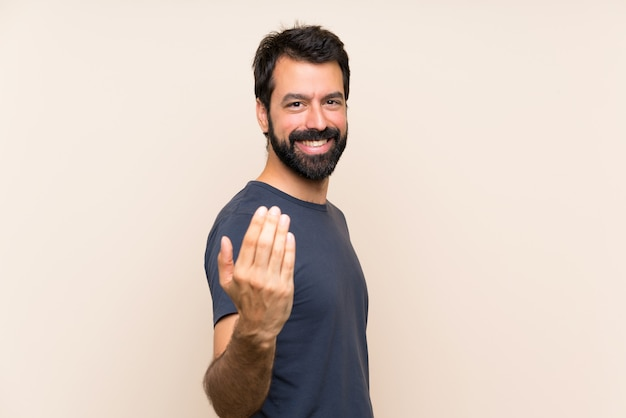 Man with beard inviting to come with hand, happy that you came