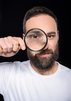 A man with a beard is looking through magnifying glass.