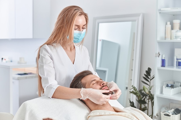 Man with beard is lying on back, getting face lifting massage. facial massage beauty treatment. wellness, beauty and relaxation concept.