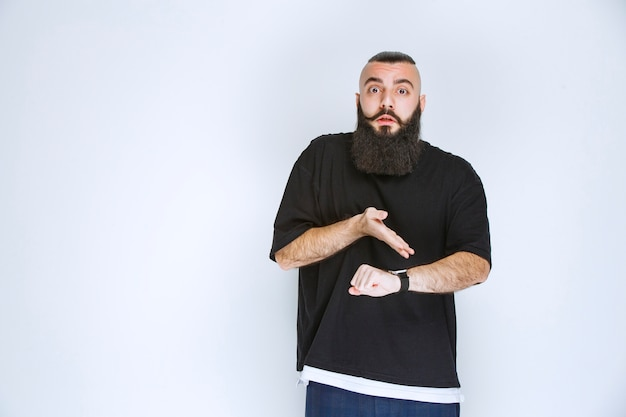 Man with beard is waiting and pointing at his time.