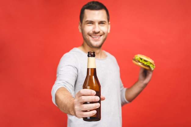 Man with a beard isolated over red background holds a hamburger and a bottle of beer, portrait