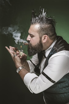 Man with a beard lighting a cigar.