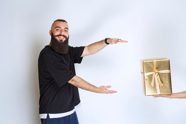 Uomo con la barba desideroso di prendere una scatola regalo d'oro offertagli.