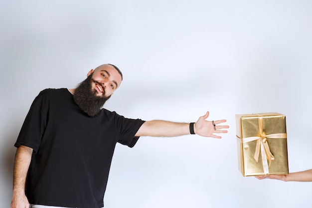 Man with beard longing forward to take a golden gift box offered to him.