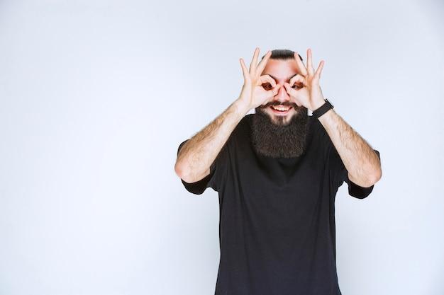 ひげを生やした男が指の間を見ています。