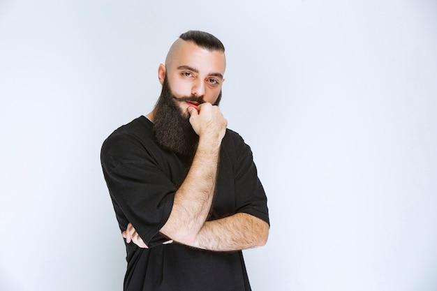 Мужчина с бородой выглядит агрессивным и разочарованным.