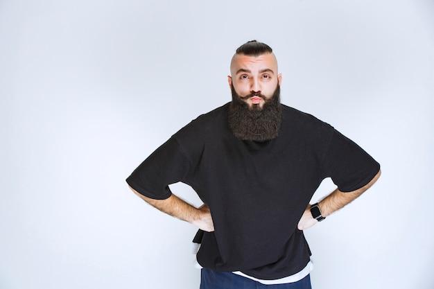 あごひげを生やした男は攻撃的で失望しているように見えます。