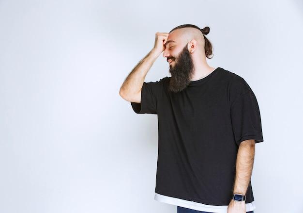 Man with beard looks sleepy and tired.