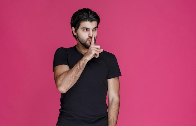 沈黙のサインを作るか、大音量を指しているひげを持つ男。