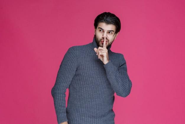 침묵 기호를 만들거나 높은 볼륨을 가리키는 수염을 가진 남자.