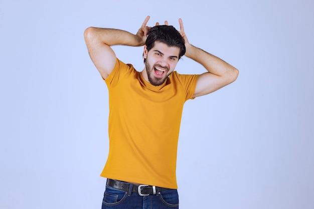 Uomo con la barba che fa il segno del lupo o del coniglio