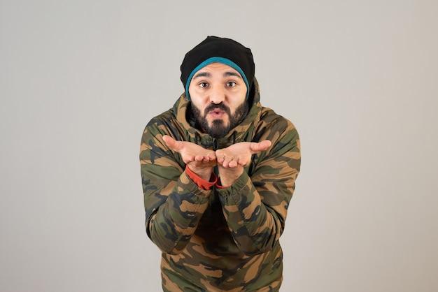 Un uomo con la barba in una giacca militare in piedi e che soffia un bacio d'aria.