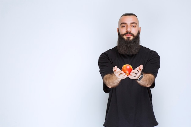 Man with beard offering a red apple or peach.