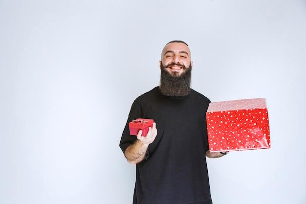 Uomo con la barba che offre una confezione regalo rossa