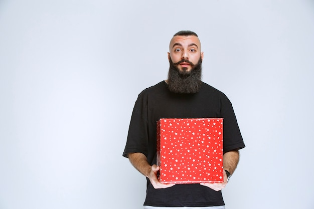 赤いギフトボックスを提供するひげを持つ男
