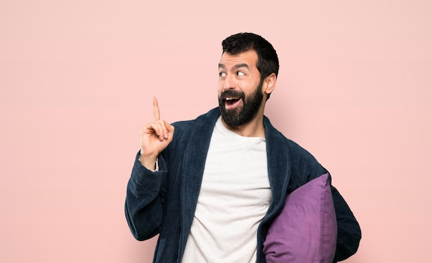 Man with beard in pajamas intending to realizes the solution while lifting a finger up over isolated pink background