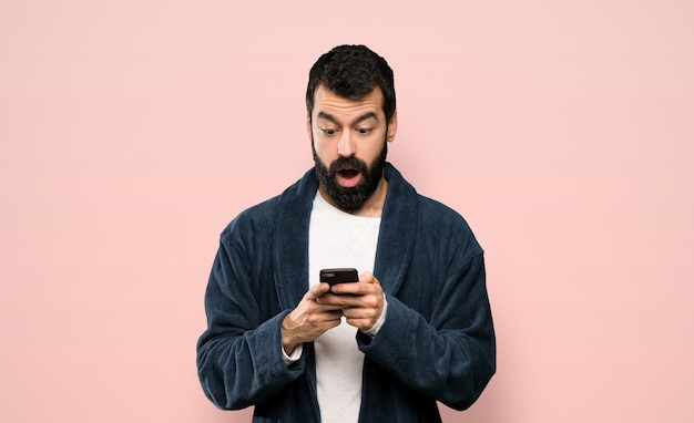 Man with beard in pajamas surprised and sending a message over isolated pink background