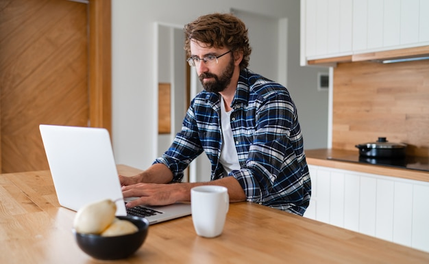 Man with beard in plaid shirt using laptop in the kitchen.