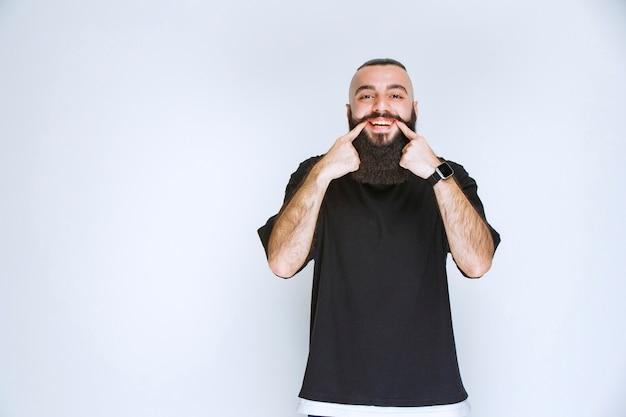 彼の笑顔を指しているひげを持つ男。