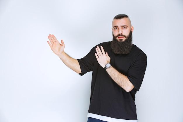 あごひげを生やした男が周りの誰かを指しています。
