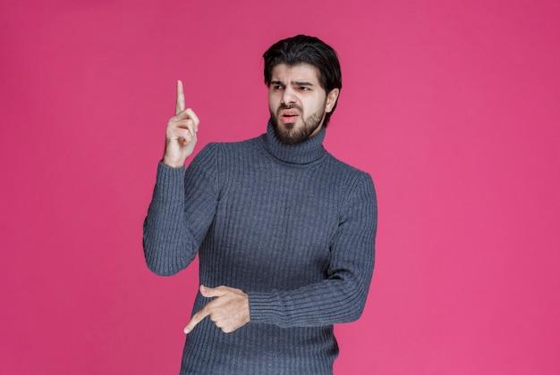 あごひげを生やして何かを指している、または誰かを紹介している男性。