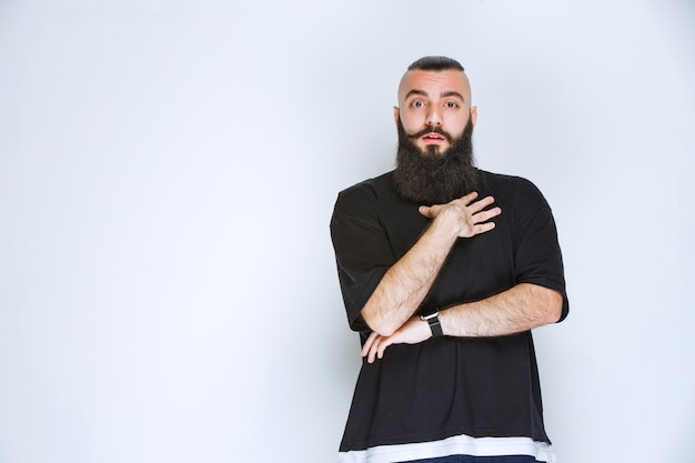 Man with beard pointing at himself.