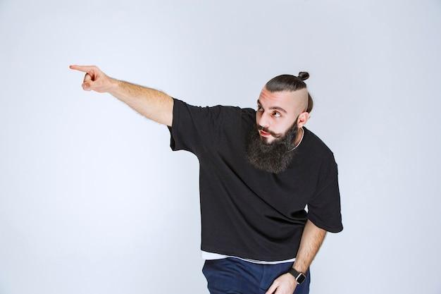 Uomo con la barba che indica qualcuno intorno.