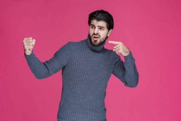 Uomo con la barba che indica qualcosa o che presenta qualcuno.