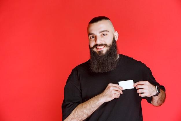 彼の名刺を提示するひげを持つ男。