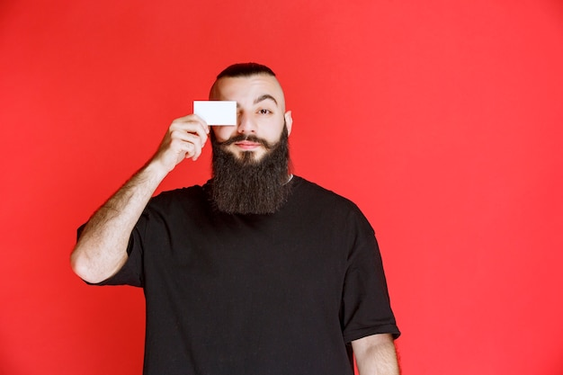 Man with beard presenting his business card.
