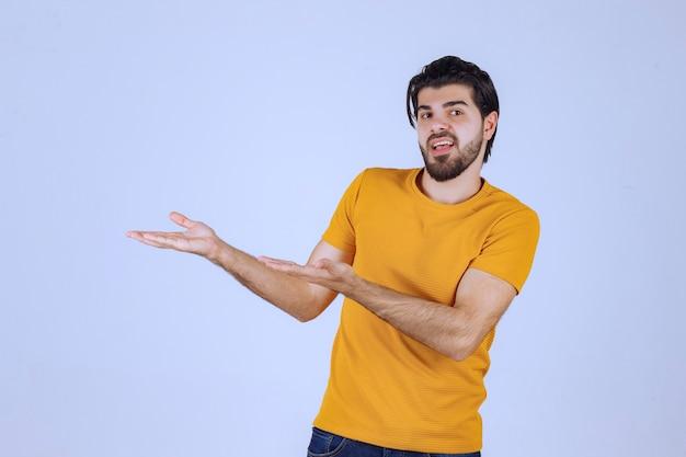 Человек с бородой, представляя что-то в его открытой руке