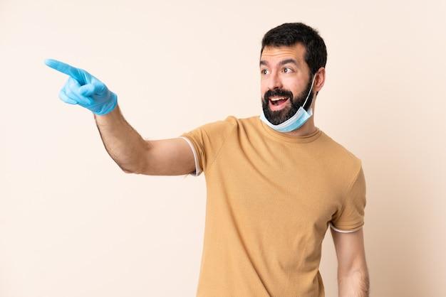 向こうを指している孤立した壁の上のマスクと手袋でコロナウイルスから保護するひげを持つ男
