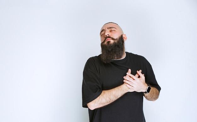 Uomo con la barba che si mette mano al cuore.