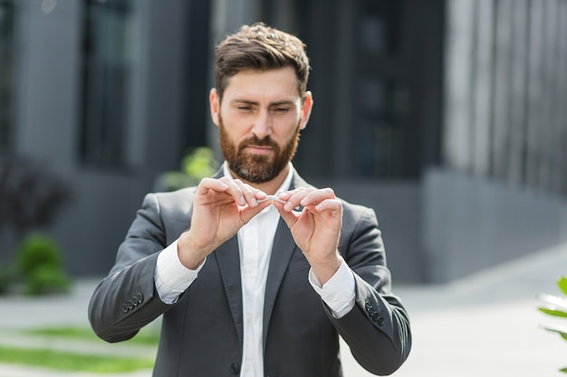 A man with a beard quit smoking cigarettes, breaks a cigarette with his hands, fights smoking