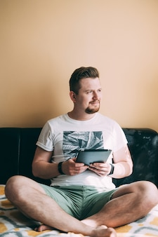 A man with a beard in shorts and a white t-shirt is sitting on the bed with a tablet and looking thoughtfully out the window.