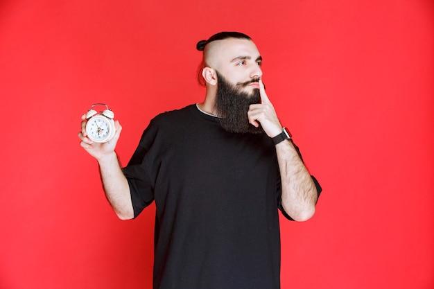 Человек с бородой показывает будильник и просит тишины.