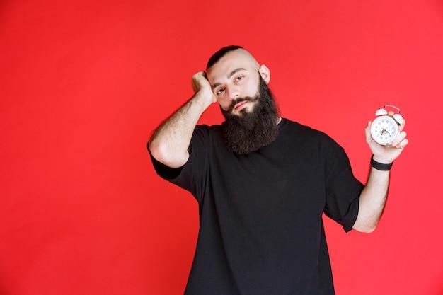 Man with beard showing alarm clock and sleeping.
