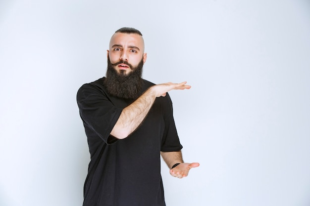 Man with beard showing the dimensions of an object.