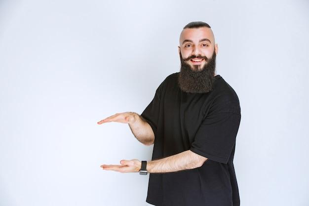 Uomo con barba che mostra le dimensioni di un oggetto.