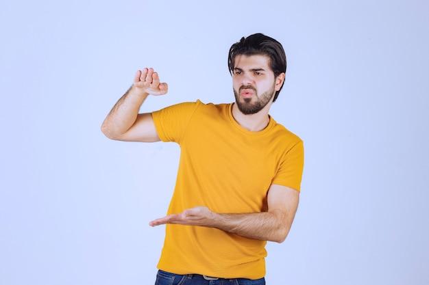 Мужчина с бородой показывает примерные размеры объекта.