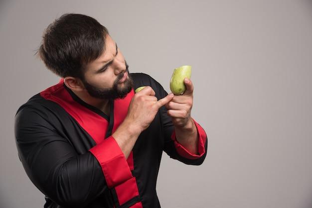 Man with beard showing on half cut zucchini .