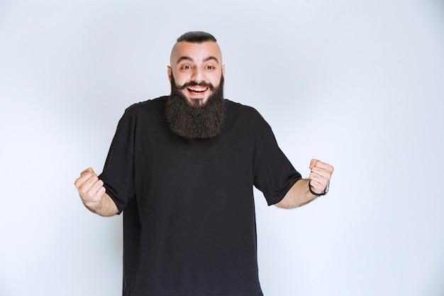 Uomo con la barba che mostra il pugno e sembra potente.