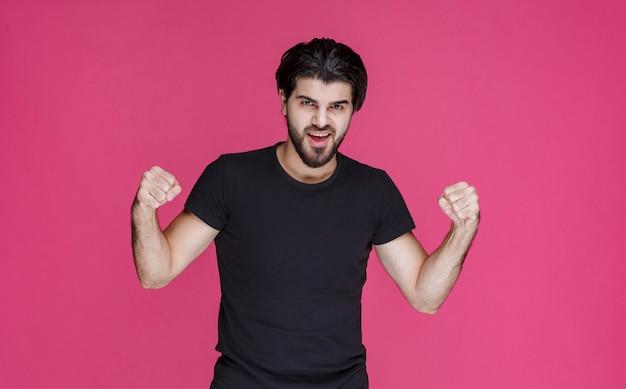 Мужчина с бородой показывает кулаки и чувствует себя сильным