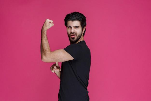 Uomo con la barba che mostra i pugni e si sente potente