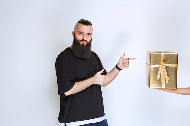 Man with beard showing his golden wrap gift box.