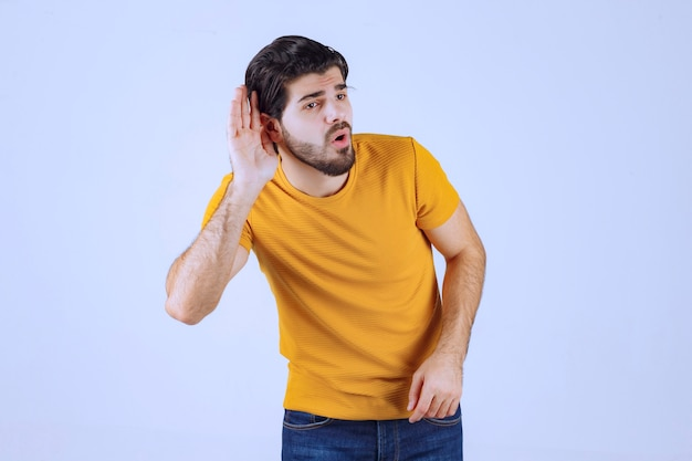 Uomo con la barba che mostra il suo udito e cerca di ascoltare attentamente