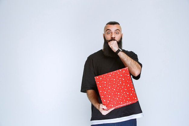 Man with beard showing his red gift box.