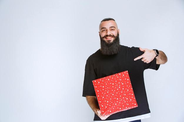 Uomo con la barba che mostra la sua confezione regalo rossa.